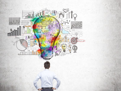 Creative business idea concept with businessman looking at colorful light bulb sketch and business charts on concrete background
